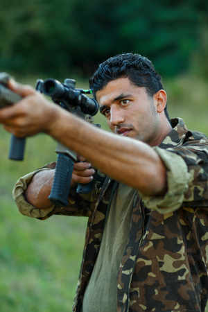 one armed: Man of Arab nationality in camouflage with a gun for trap shooting aiming at a target