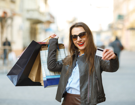 gift spending: Sale, shopping, tourism and happy people concept - beautiful woman with shopping bags and credit card in the hands on a street