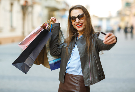 on duty: Sale, shopping, tourism and happy people concept - beautiful woman with shopping bags and credit card in the hands on a street