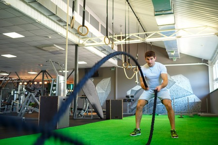 Athletic man with battle rope in functional training fitness gym