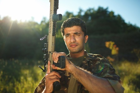 one armed: Man of Arab nationality in camouflage with a shotgun in an outdoor