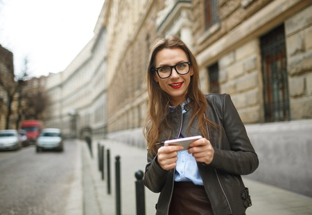 sidewalk talk: Businesswoman walking down the street while talking on smart phone. Happy smiling caucasian business woman busy