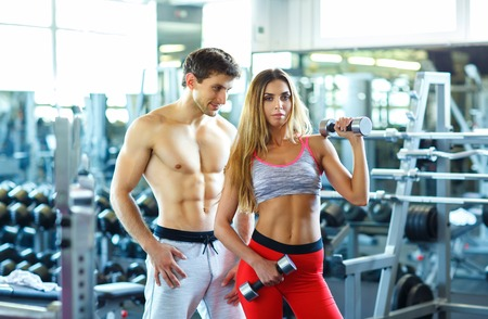 healthy men: Athletic couple - man and woman with dumbbell in the gym background