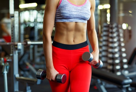 Beautiful slim woman with dumbbell in the gym doing exercises Stock Photo