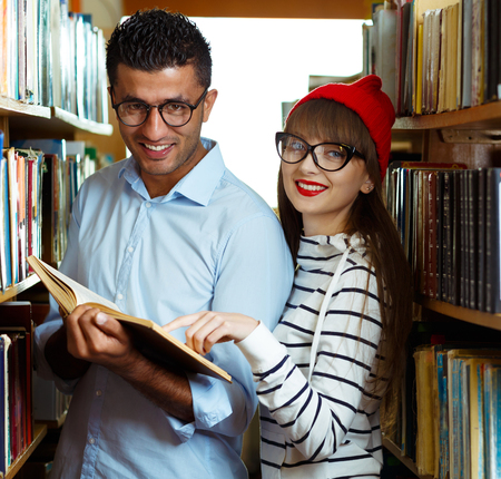 Young student couple choosing books between the shelves in the library photo