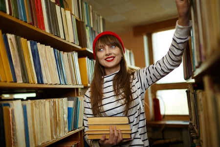 Young student girl choosing books between the shelves in the library photo