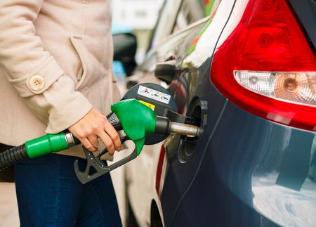 fills: Woman fills petrol into her car at a gas station closeup