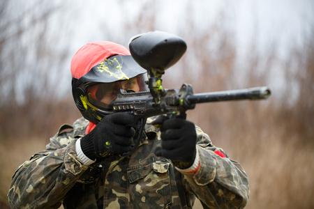 보호 마스크를 목표로 총을 입고 페인트 볼 스포츠 선수 스톡 콘텐츠