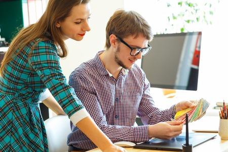 colega joven - hombre y una mujer mirando a una paleta de color de la pintura en la oficina en casa, concepto de negocio moderno