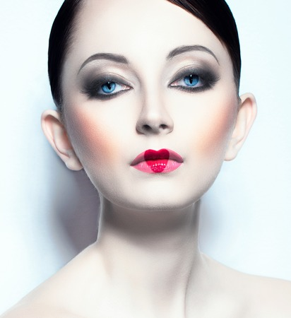 Portrait of a beautiful young woman like doll with a glamorous cool makeup photo