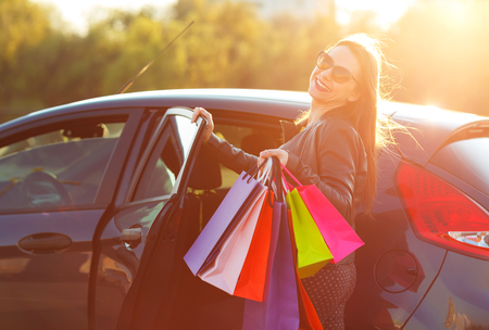 go to the shopping: Smiling Caucasian woman putting her shopping bags into the car - Lets go shopping concept