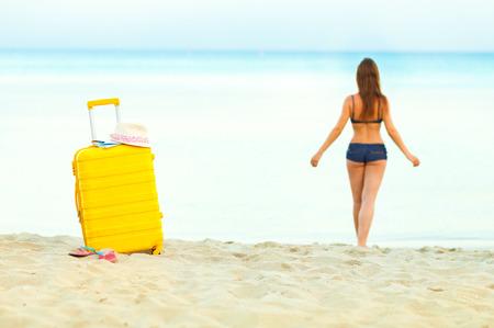 Maleta amarilla brillante en la playa y una niña entra al mar en el fondo Foto de archivo