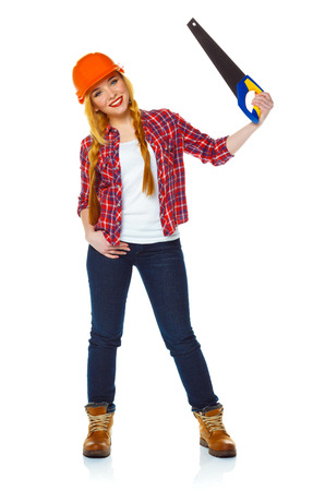 Young funny woman in helmet with a saw on a white background Stock Photo