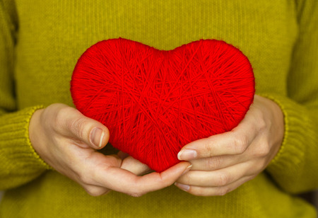 Closeup on red heart made from wool in hand of woman. Image of Valentines day