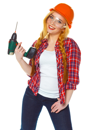 Female construction worker in a hard hat with a perforator Stock Photo