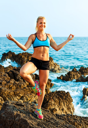 yoga rocks: Happy athletic woman relaxing - practicing yoga on the rocks by the sea