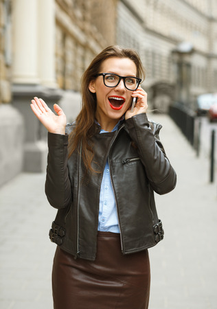 sidewalk talk: Surprised businesswoman walking down the street while talking on smart phone Stock Photo