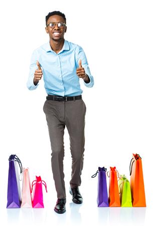 Glücklich African American Mann mit Einkaufstüten auf weißem Hintergrund. Weihnachten und Urlaub Konzept