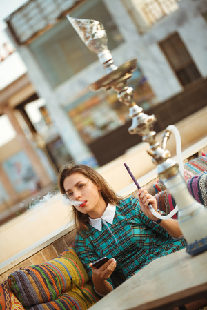 Beautiful young woman smokes a hookah in a cafe, Egypt