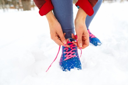 Running shoes - woman tying shoe laces. Closeup of female sport fitness runner getting ready for jogging outdoors on park in winter Stock Photo