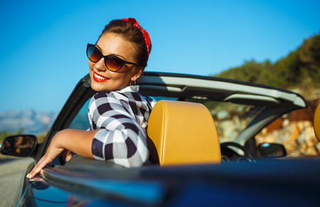 caras emociones: Beautiful pin up woman sitting in cabriolet, enjoying trip on luxury modern car with open roof, fashionable lifestyle concept