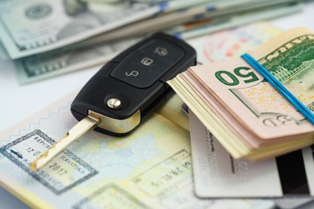 American money, credit cards and car key lies on thr top of the opened passport - travel concept Stock Photo