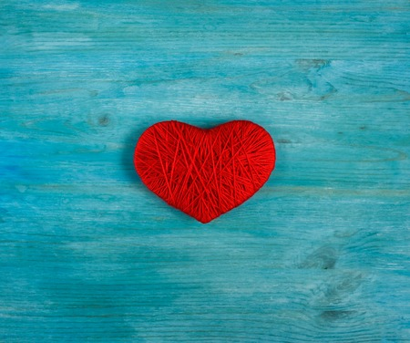 Red heart shape made from wool on blue wooden background. Concept of Valentines day