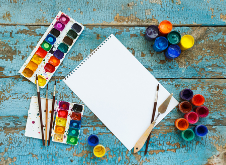Art of Painting. Painting set: brushes, paints, crayons, watercolor, white paper on a blue wooden background