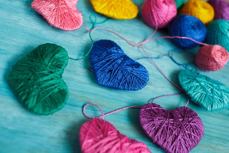 Multicolored Hearts with a balls of thread on blue wooden background. Image of Valentines day