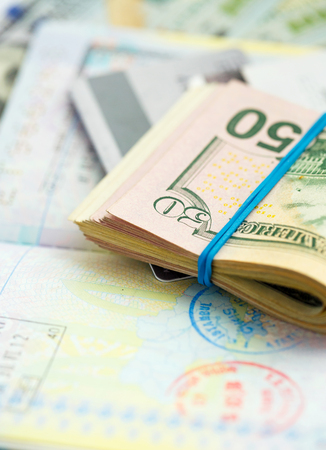 American money and credit cards lie on the top of the opened passport - travel concept Stock Photo