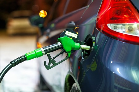 Car refueling on a petrol station in winter at night closeup Stock Photo