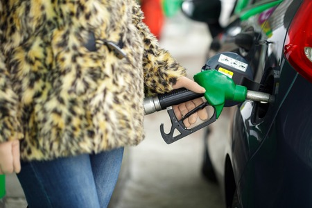 Woman fills petrol into her car at a gas station in winter closeup Stock Photo