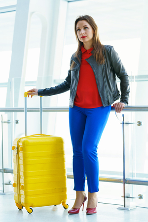 Woman in bright clothes with yellow suitcase stands in the airport building