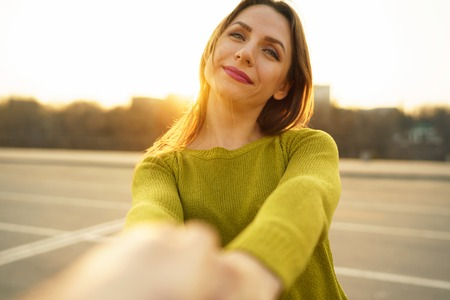 Follow me - happy young woman pulling guys hand - hand in hand walking on a bright sunny day - concept of carefree modern life Stock Photo