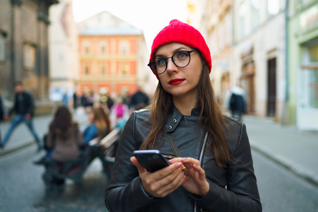 sidewalk talk: Beautiful woman with red lips and red hat uses smartphone and strolls along the medieval street