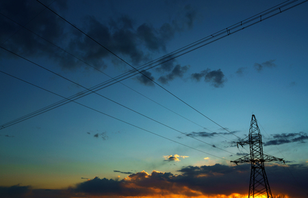 power cables: Power lines against the sky at sunset or at sunrise Stock Photo