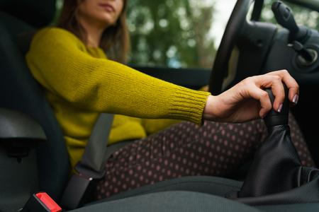 여자가 차를 운전하고 변속기에 변속 기어 스톡 콘텐츠