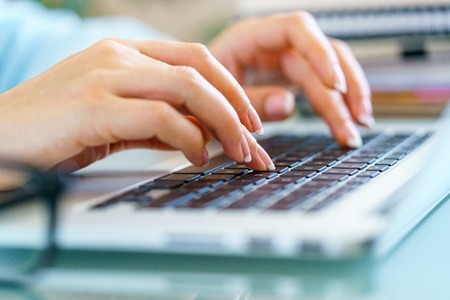 Closeup of typing female hands on laptop