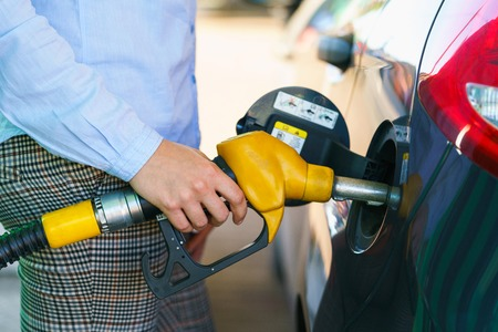 unleaded: Woman fills petrol into her car at a gas station