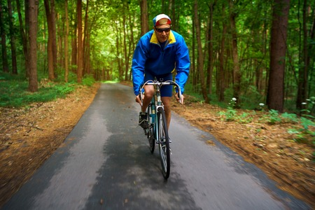 Middle-aged man is riding a road bike along a forest road. Excellent training and healthy exercise