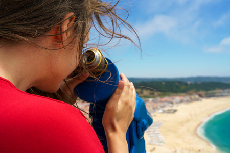 using binoculars: Beautiful female tourist using coin paid binoculars on high hill and looking at cityscape of Nazareth, Portugal