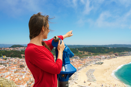 Beautiful female tourist using coin paid binoculars on high hill and looking at cityscape of Nazareth, Portugal