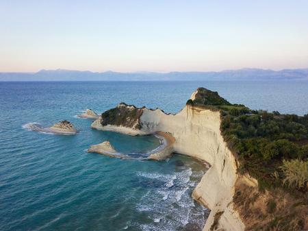 paleokastritsa: Aerial photo of Cape Drastis at Corfu island in Greece at sunset. Picturesque coast of Corfu island. Beautiful sea landscape