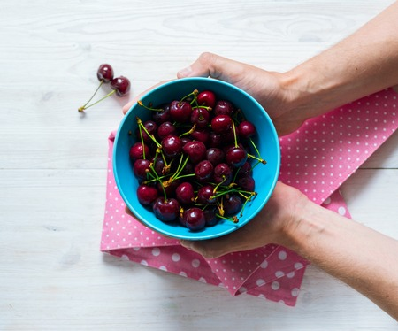 Female hands hold a blue bowl with ripe sweet cherry Imagens