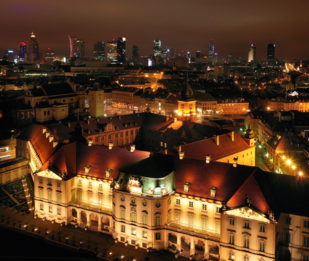 Aerial view of the royal castle in the old town at night, Warsaw, Poland. In the background are visible modern skyscrapers, downtown Imagens