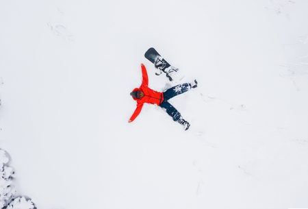 Aerial view of a man who lies in the snow with his arms outstretched next to his snowboard