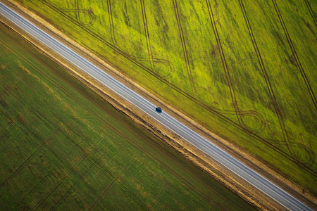 Aerial view of a car driving along a rural road between two fields