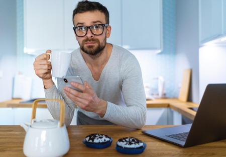 Bearded man having breakfast in the kitchen and using smartphone at the same time Imagens