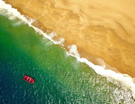 Top view of a lonely red boat anchored off the coast of golden ocean beach. Imagens