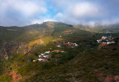 Aerial view of a village in mountains covered in sparse vegetation. Tenerife, Canary Islands, Spain